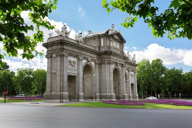 背後にレティーロ公園があるプエルタデアルカラの珍しい景色。マドリッドの街の有名な場所。 Premium写真