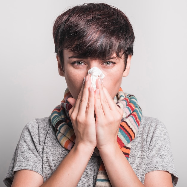Unwell young woman blowing her nose against gray background Free Photo