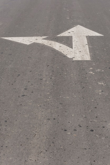 Up and left pointing arrows on asphalt Free Photo