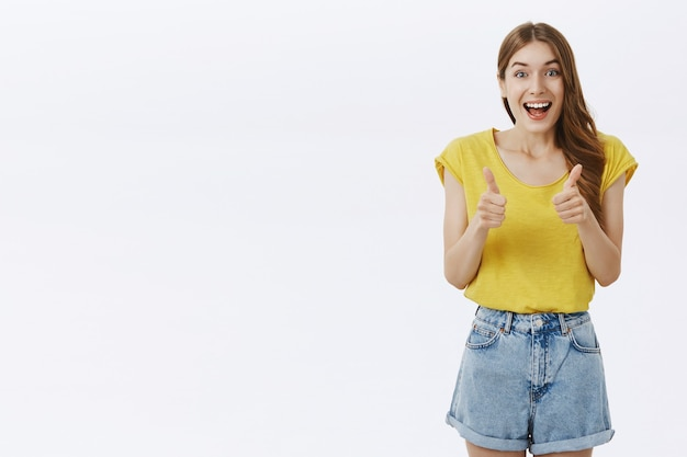 Upbeat beautiful girl showing thumbs-up in approval, like idea, agree or recommend something awesome Free Photo