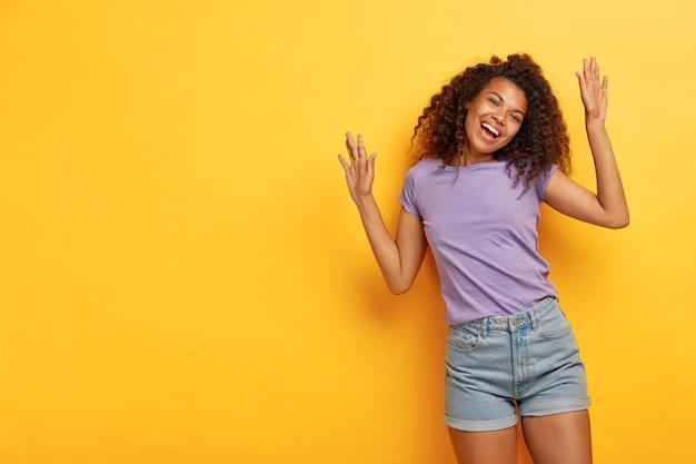 明るい陽気な巻き毛の女性は腕を上げ、大喜びを感じ、活発に踊り、パーティーで楽しんで、カジュアルな紫色のtシャツとジーンズのショートパンツを着ています 無料写真
