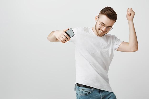 Жизнерадостный красивый парень в очках танцует под музыку в беспроводных наушниках с мобильным телефоном в руке Бесплатные Фотографии