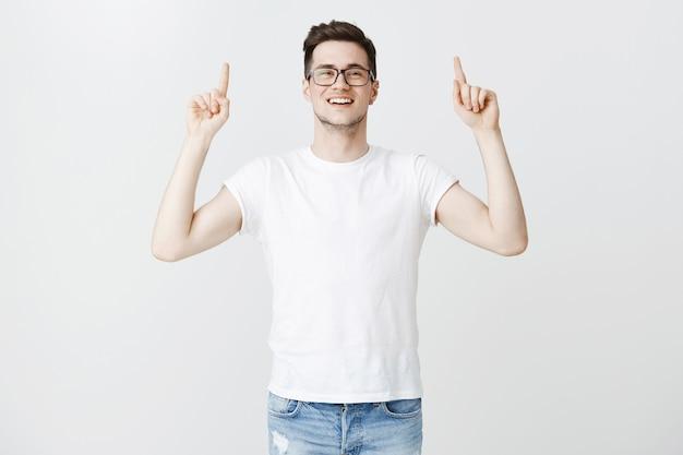 Allegro bel giovane con gli occhiali che punta il dito verso l'alto Foto Gratuite