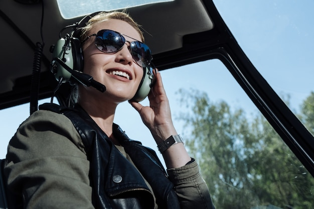 Upbeat mood. beautiful helicopter pilot smiling cheerfully while listening to air traffic controller in her headphones Premium Photo