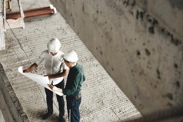 성인 Arhitecht와 그의 작업자가 작업 현장에 건설중인 건물에 대해 이야기하는 상단보기. 프리미엄 사진