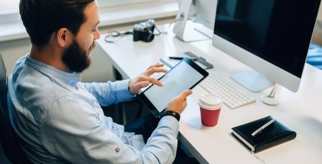 Верхний вид портрет бородатого мужчины с помощью планшета, пьющего кофе в своем офисе Premium Фотографии