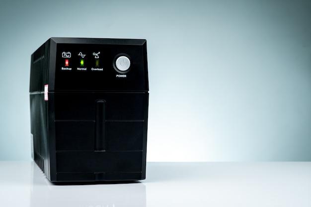 無停電電源装置。テーブルに分離されたバッテリーを備えたバックアップ電源ups。 pc用のups。セキュリティのためのオフィスのコンピューターシステムの機器。家庭からデータセンターまでの電源保護ソリューション。 Premium写真