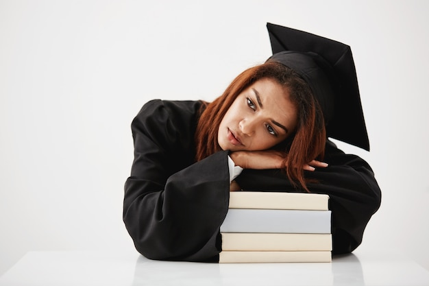 Расстроен африканских выпускник, лежа на книгах мышления сидя. копировать пространство Бесплатные Фотографии