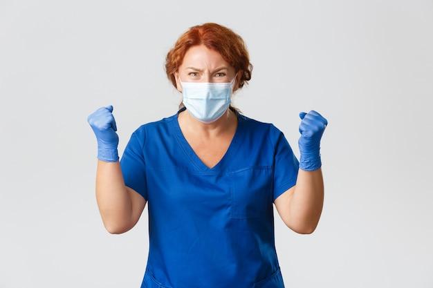 Расстроенная и разочарованная женщина-врач выглядит напряженной, напряженной, чего-то ждала, получает плохие новости, сжимая кулаки в недовольстве. Premium Фотографии