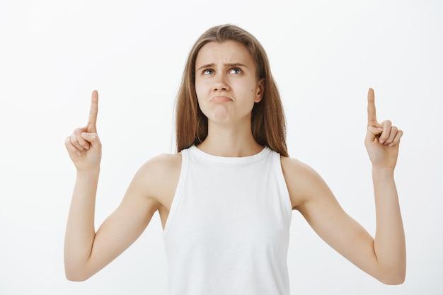 제품에 대해 불평하고, 손가락을 아래로 가리키고, 불쾌한 찡그린 얼굴을하는 화가 나고 실망한 소녀 무료 사진