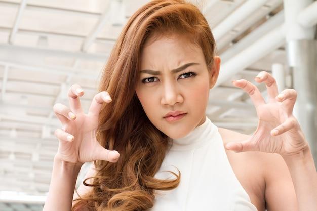 Расстроенная, сердитая женщина готова причинить тебе боль когтями Premium Фотографии