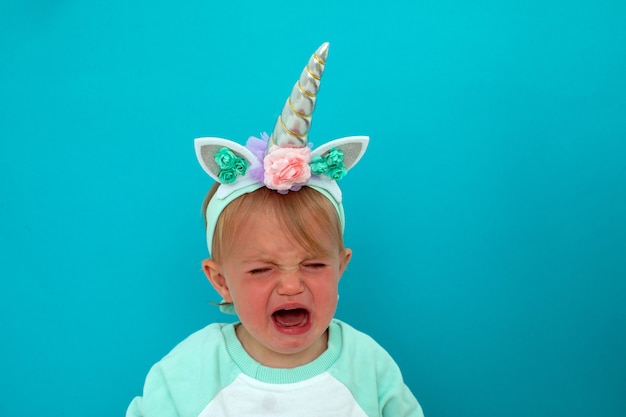 Upset baby with open mouth and eyes closed in unicorn costume crying on blue Premium Photo
