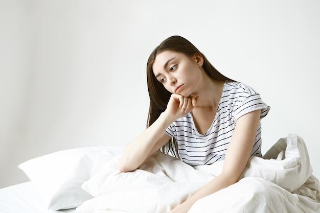 긴 갈색 머리가 침대에 앉아 잠겨있는 모습, 일하러 가고 싶지 않고 지루하고 단조로운 삶에 피곤함을 느끼는 아름다운 젊은 여성을 화나게합니다. 무료 사진