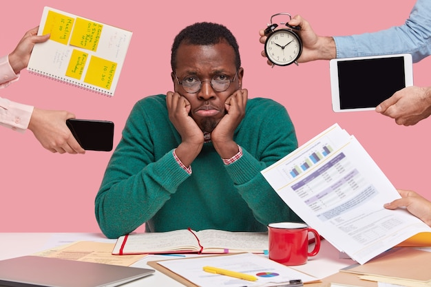 Upset black male worker has much work, thinks about business project, being lack of time Free Photo