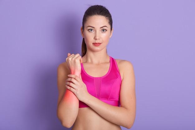 Расстроенная брюнетка молодая женщина повредила руку во время спортивной тренировки Бесплатные Фотографии