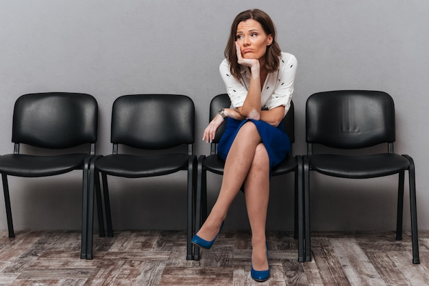 Upset business woman waiting on chairs Free Photo