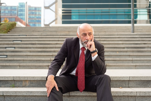 Upset businessman sitting in steps Free Photo