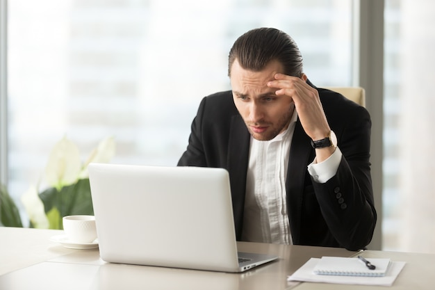 Upset confused businessman looking at laptop screen Free Photo