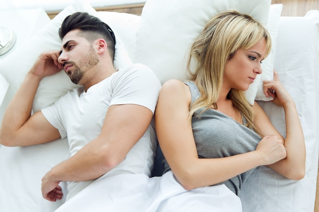 Upset couple lying back to back in bed Free Photo