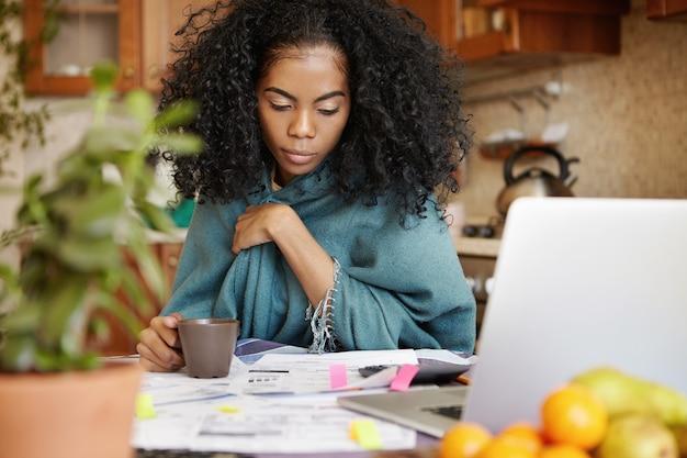 Расстроенная темнокожая домохозяйка с афро-прической пьет кофе, управляя домашним бюджетом поздно ночью Бесплатные Фотографии