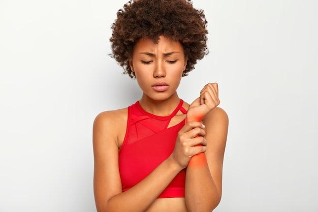 화가 난 불쾌한 여성이 다친 손을 만지고, 빨간색으로 표시된 손목에 문제가있는 고통스러운 영역을 보여주고, 캐주얼 한상의를 입고, 끔찍한 고통을 겪습니다. 무료 사진