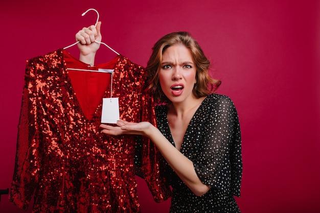 洋服店の価格に腹を立てているヨーロッパの女の子を怒らせる 無料写真