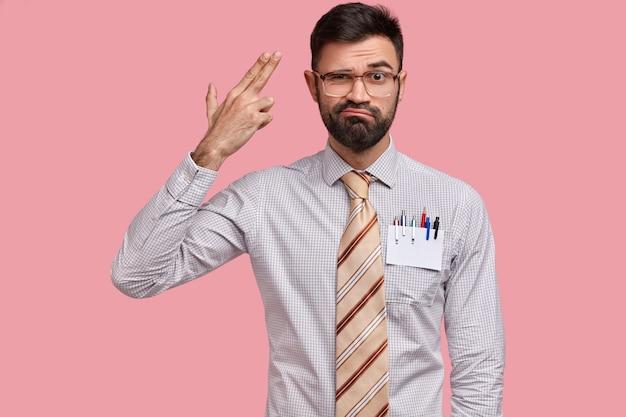 Un uomo europeo sconvolto con setole spesse fa un gesto di suicidio, si spara nel tempio, ha un'espressione del viso dispiaciuta, indossa abiti formali Foto Gratuite