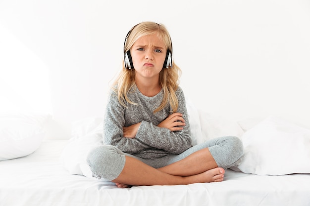 Upset female kid in headphones sitting with crossed arms and legs in bed, Free Photo