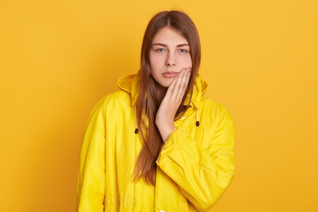 Upset female wearing yellow jacket touching her cheek, suffering from toothache, having medical problems, standing against yellow wall. Free Photo
