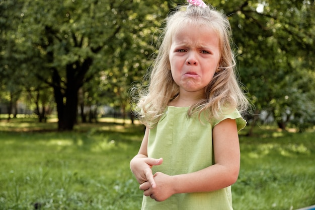 Upset girl child crying in the park. parenting, child psychology. Premium Photo