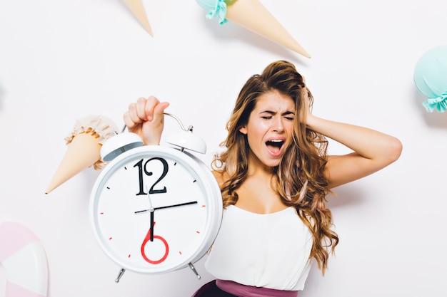 Расстроенная девушка кричит с закрытыми глазами, в панике трогает голову и держит большие белые часы. портрет несчастной молодой женщины в белой майке Бесплатные Фотографии