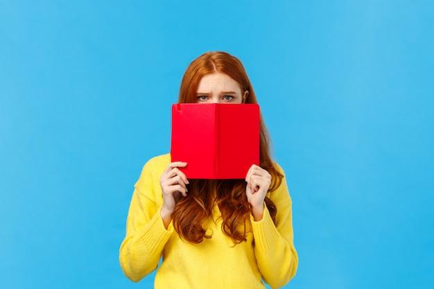 Расстроенная мрачная и неловкая милая надутая рыжая женщина, нахмурившись, не хочет говорить с тобой Premium Фотографии