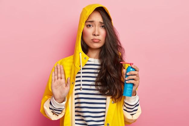 La donna asiatica cupa sconvolta fa il gesto di rifiuto, dice di no, tiene uno spray medico per evitare la malattia, indossa un impermeabile giallo impermeabile con cappuccio, maglione a righe Foto Gratuite