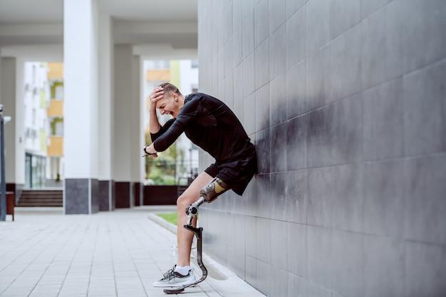 壁に寄りかかって頭を抱えていると腕時計を見て義足で動揺のハンサムな白人のスポーツマン。 Premium写真