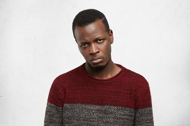 彼の友人が彼をパーティーに招待しなかったので、失望と悲しみを見てカジュアルなセーターに身を包んだ不満と裏切られた動揺のハンサムな若い黒肌の男性 無料写真