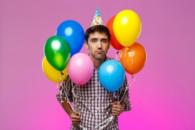 화가 남자 생일을 축 하, 보라색 벽 위에 다채로운 Baloons를 들고. 무료 사진