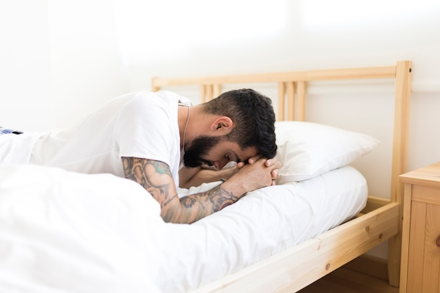 Upset man lying on bed in bedroom Free Photo
