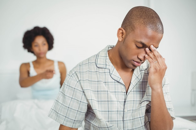 Upset man sitting on bed after arguing with his girlfriend Premium Photo