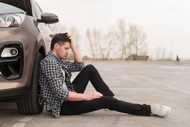 Upset man sitting beside broken down car Free Photo