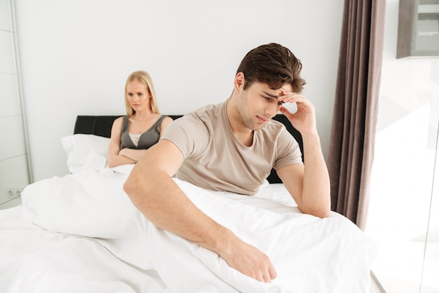 Upset man sitting with his sad woman in bed at home Free Photo