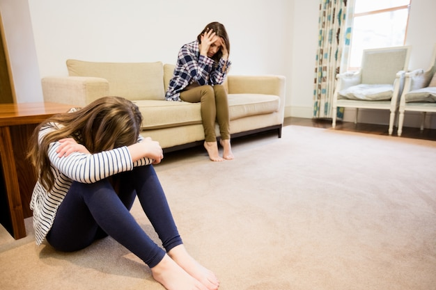 Upset mother and daughter sitting in living room Free Photo