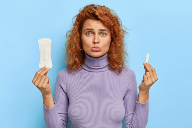 Upset redhead woman holds hygienic sanitary pad and tampon, chooses good protection during red days, has gloomy face expression, wears casual jumper, isolated on blue wall. feminity concept Free Photo