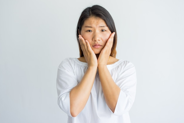 upset shocked young asian woman touching cheeks and looking at