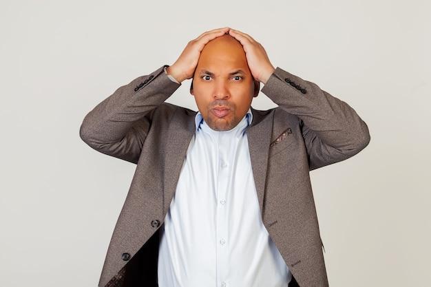 Расстроенный шокированный молодой бизнесмен, взявшись за голову руками, был шокирован, нахмурившись и схватившись за голову. Premium Фотографии