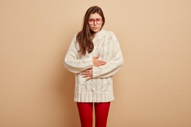 화가 난 유럽 여성은 고통으로 배를 만지고, 상한 제품을 먹은 후 불편 함을 느끼고, 안경과 따뜻한 옷을 입고, 갈색 벽 위에 선다. 복통 개념 무료 사진