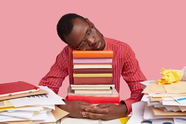 Uomo nero stanco sconvolto fa un pisolino su una pila di libri, dorme dopo aver studiato tutta la notte, preparato per gli esami Foto Gratuite