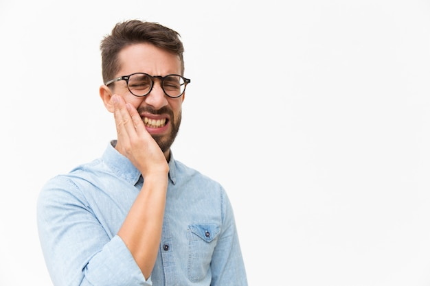 Upset unhappy guy holding cheek with pain face Free Photo