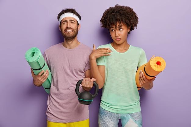 動揺した無精ひげを生やした男は、巻き上げられたカレマットを保持し、体重を持ち上げ、スポーツに参加し、紫色の背景に対して隣り合って立ち、tシャツを着て、フィットネストレーニングを受けます。人、スポーツ、モチベーション 無料写真