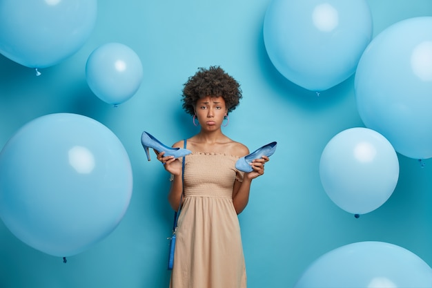 Free Photo   Upset woman got calluses while wearing high heel shoes, wears cocktail dress, has bad mood, tired after party, isolated on blue wall decorated with inflated balloons. women clothes collection