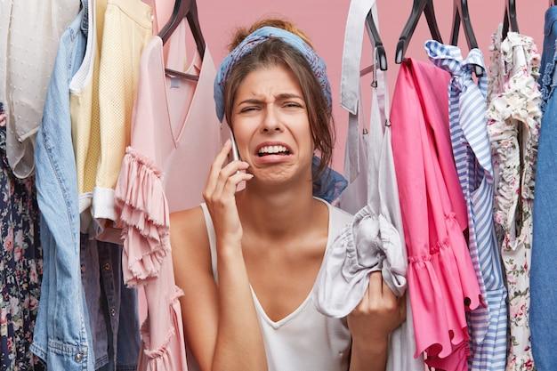 Расстроенная женщина стоит возле вешалки, болтает по смартфону с подругой, жалуется, что ей нечего надеть. недовольная женщина, не зная, что надеть на день рождения Бесплатные Фотографии